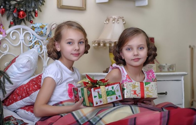 19139907 - two girls consider christmas gifts in the morning in bed