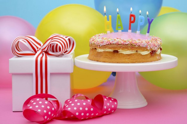 43184178 - bright colorful party table with balloons and gifts with bright color ribbons and bows, and happy birthday cake on cake stand.